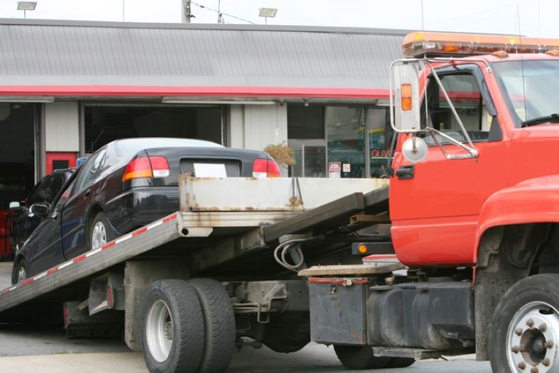 Black car on a red flat bed tow truck